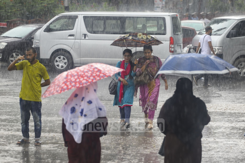 Pedestrians carrying umbrellas cross the road at Shahbagh in Dhaka amid sporadic rains on Sunday. Photo: Asif Mahmud Ove