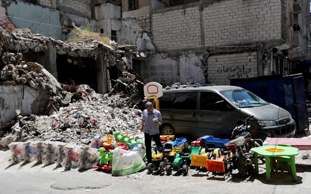 FILE PHOTO: A street vendor sells toys next to rubble of damaged buildings in the city of Idlib, Syria May 25, 2019. REUTERS