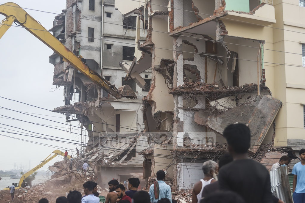 BIWTA workers bulldozed a number of buildings, including some with multiple storeys, at Kholamora Gudaraghat in Dhaka's Kamrangirchar on Tuesday as part of an eviction drive to free the banks of the Buriganga River from illegal structures. Photo: Abdullah Al Momin