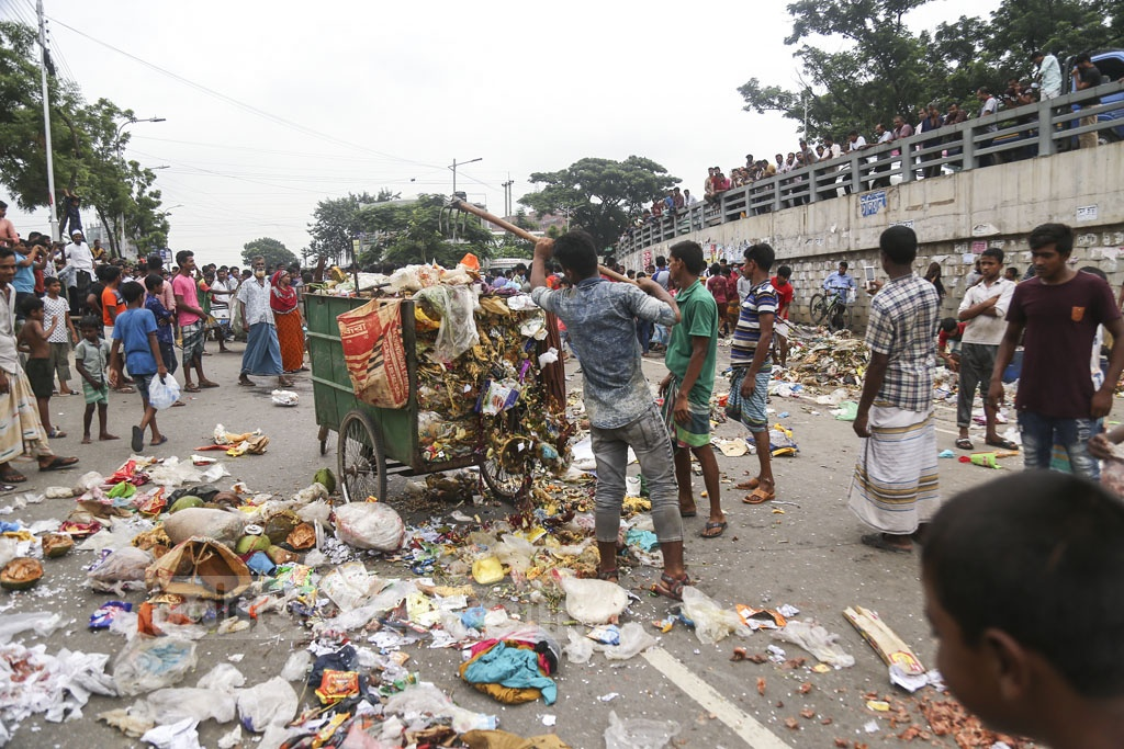 Rickshaw-pullers put garbage from a van to block Rampura TV Road on Tuesday in protest against a ban on rickshaw movement on three important streets in the capital. Photo: Mahmud Zaman Ovi