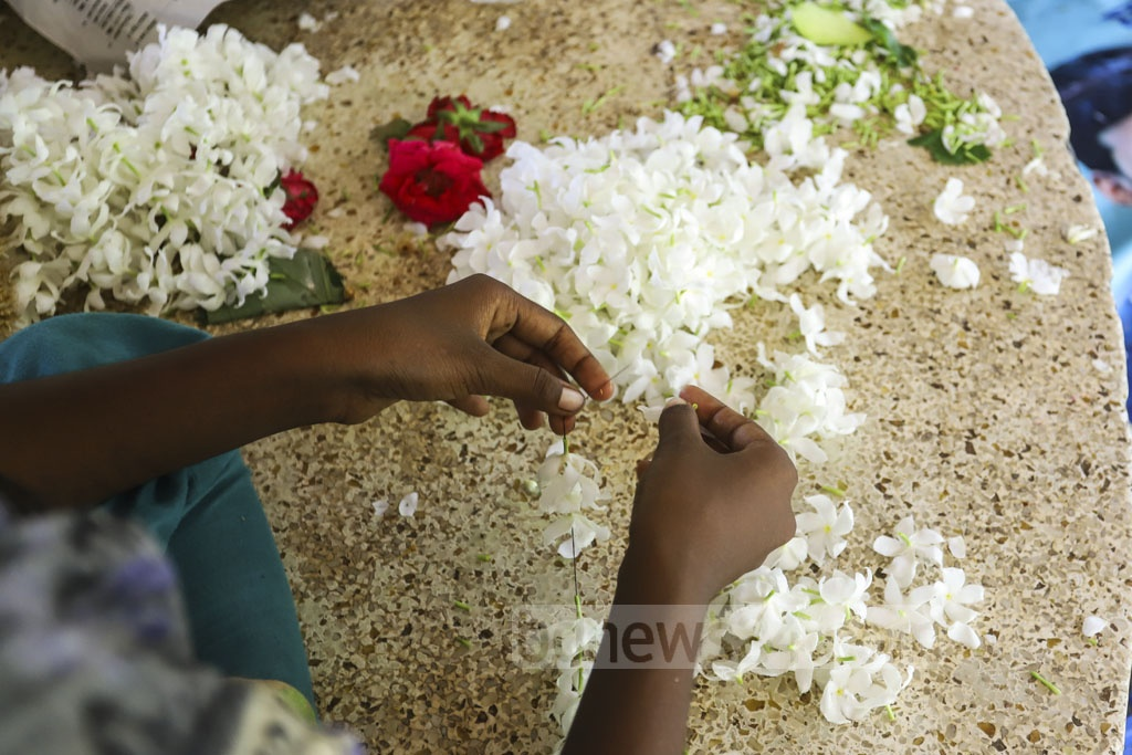 Homeless people make garlands with flowers collected from the Suhrawardy Udyan in Dhaka. They earn Tk 5-10 per garland. Photo: Asif Mahmud Ove