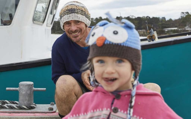 Matt Zurbo and his daughter Cielo, on a pier in Eaglehawk Neck, Tasmania on June 5, 2019. Cielo is the daughter for whom his writing project is named after. Zurbo spent years clearing trails and replanting forests in the Australian bush before landing his current job at an oyster Farm in addition to writing 365 children's books in 365 days.(Peter Tarasiuk/The New York Times)