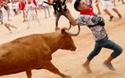 FILE PHOTO: A reveller is being hit on the bullring during the running of the bulls at the San Fermin festival in Pamplona, Spain, Jul 14, 2019. REUTERS
