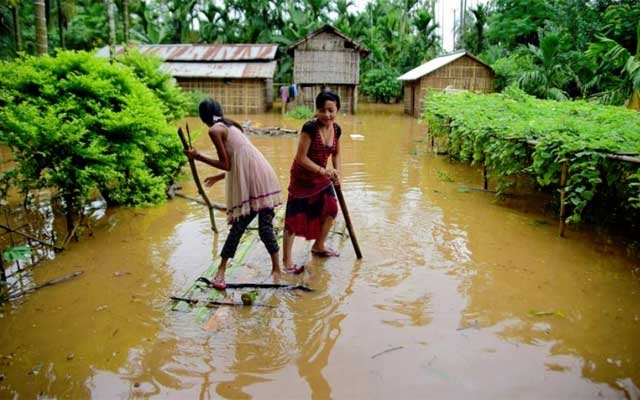 FILE PHOTO: Girls row a makeshift raft past submerged houses at a flood-affected village in Karbi Anglong district, in the northeastern state of Assam, India, Jul 11, 2019. REUTERS