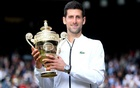 Wimbledon - All England Lawn Tennis and Croquet Club, London, Britain - July 14, 2019 Serbia's Novak Djokovic poses with the trophy as he celebrates winning the final against Switzerland's Roger Federer Laurence Griffiths/Pool via REUTERS