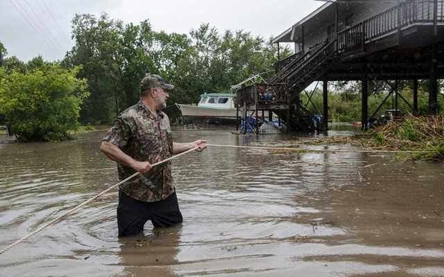Steve Viator stands in floodwaters, clearing brush after Hurricane Barry in Franklin, La, Jul 14, 2019. The New York Times