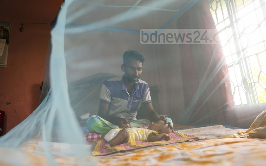 The number of dengue patients in Dhaka is on the rise. 'Saidur', a resident of Newazbagh area in Dhaka's Nandipara, is using a mosquito net in day time to save his two and a half years old daughter. Photo: Mahmud Zaman Ovi