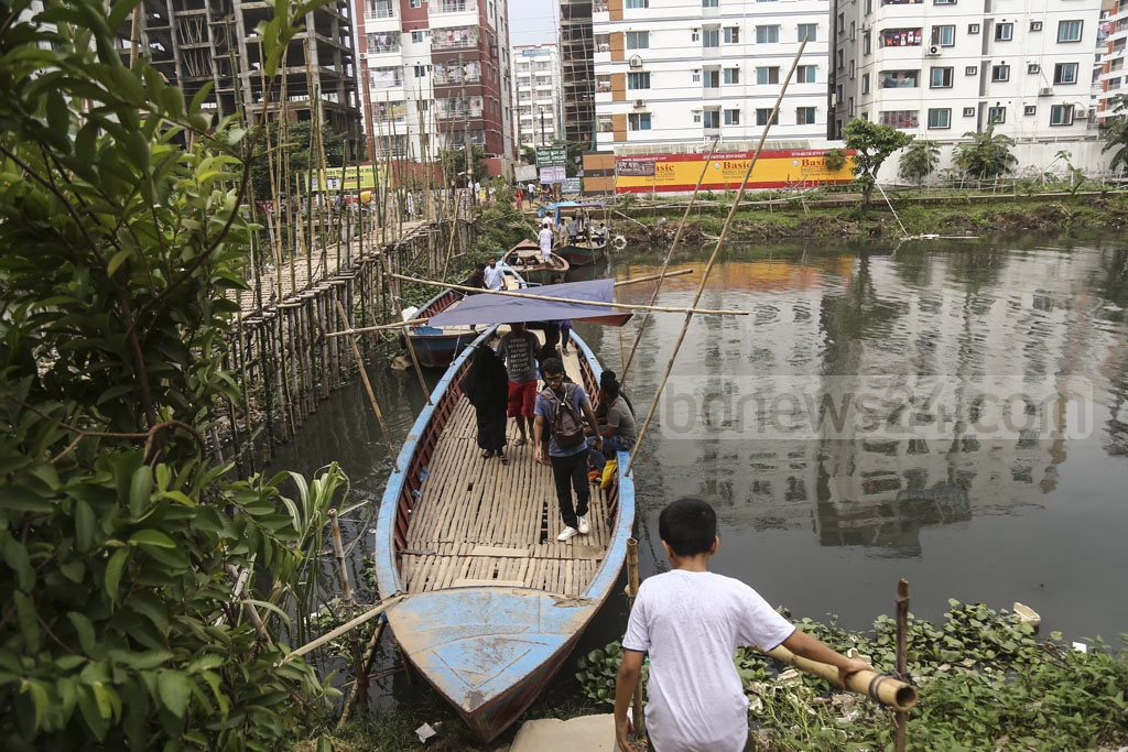 People cross a canal in Dhaka's Rampura on Tuesday by walking on anchored boats as a bamboo bridge in the area undergoes repair. Photo: Mahmud Zaman Ovi