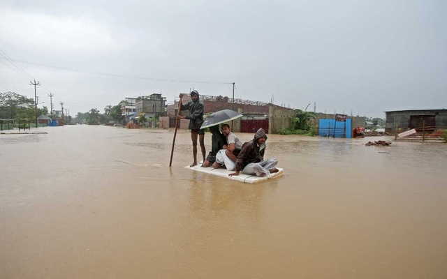 Villagers use a makeshift raft to cross a flooded area on the outskirts of Agartala, India July 15, 2019. REUTERS