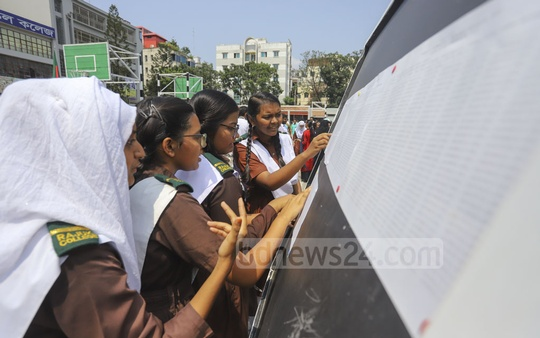 HSC candidates of Rajuk Uttara Model College in Dhaka checking their results on a notice board on Wednesday. Photo: Asif Mahmud Ove