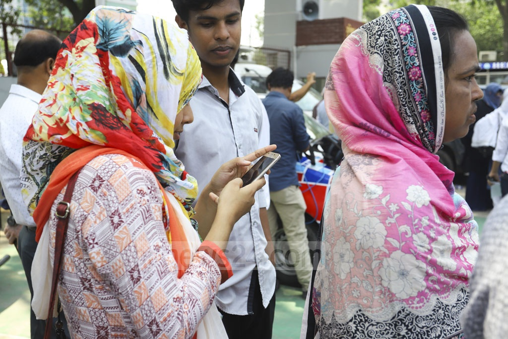 An HSC candidate of Rajuk Uttara Model College in Dhaka checking his results on mobile phone on Wednesday. Photo: Asif Mahmud Ove