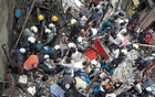 Rescue workers and residents search for survivors at the site of a collapsed building in Mumbai, India, July 16, 2019. REUTERS