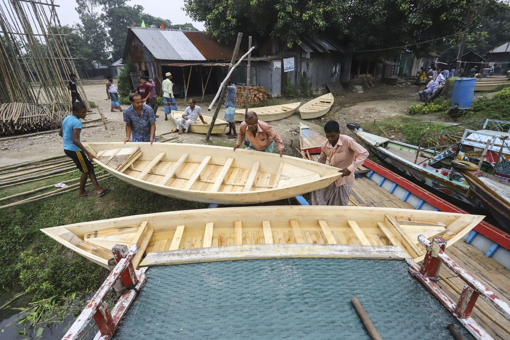 A boat is being transported on another after it was brought from a weekly market on the bank of the Balu river at Kayetpara Bazar in Nasirabad, an area under Khilgaon Police Station. Photo: Asif Mahmud Ove