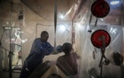 An Ebola survivor who is now immune to the virus adjusts the oxygen mask of a patient at the treatment centre in Beni, Congo, May 8, 2019. The New York Times