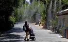 A visitor to the Phoenix Zoo walked through misting water on Tuesday. The New York Times