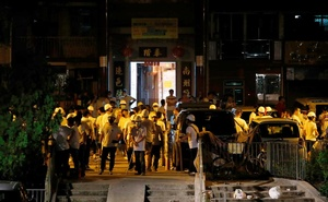 Men in white T-shirts with poles are seen in Yuen Long after attacking anti-extradition bill demonstrators at a train station, in Hong Kong, China Jul 21, 2019. REUTERS
