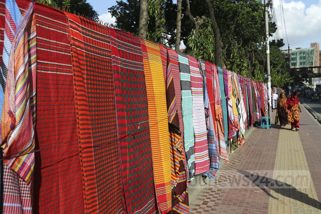 The wall of the SOS Children's Village along the street take a colourful look as seven traders put 'Gamchha', or traditional towel, on the wall by occupying no or very little space of the pavement. Photo: Mahmud Zaman Ovi