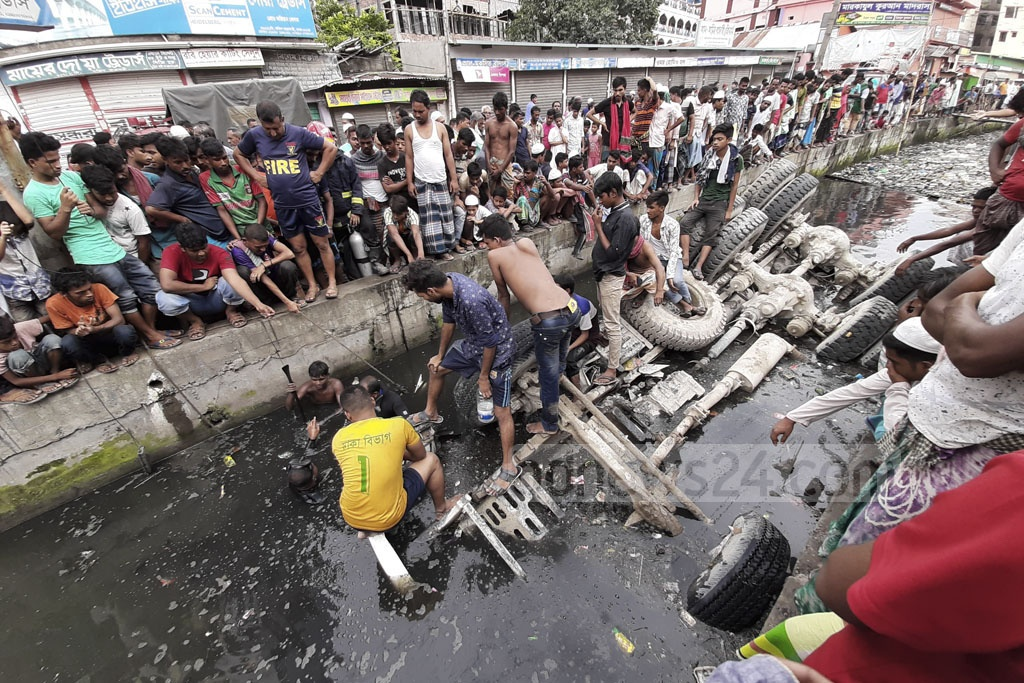 A concrete mixer overturned and partially plunged into Kutubkhali Canal at Jatrabari in Dhaka early Wednesday morning. Photo: Abdullah Al Momin
