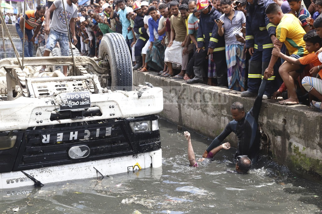 Fire Service and Civil Defence divers pulling out the body of a driver from a concrete mixer truck that overturned and partially plunged into Kutubkhali canal in Dhaka's Jatrabari on early Wednesday morning. Photo: Abdullah Al Momin