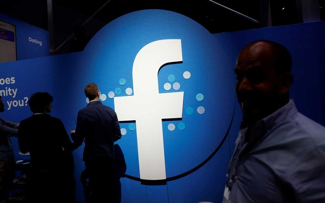 FILE PHOTO: Attendees walk past a Facebook logo during Facebook Inc's F8 developers conference in San Jose, California, US, Apr 30, 2019. REUTERS