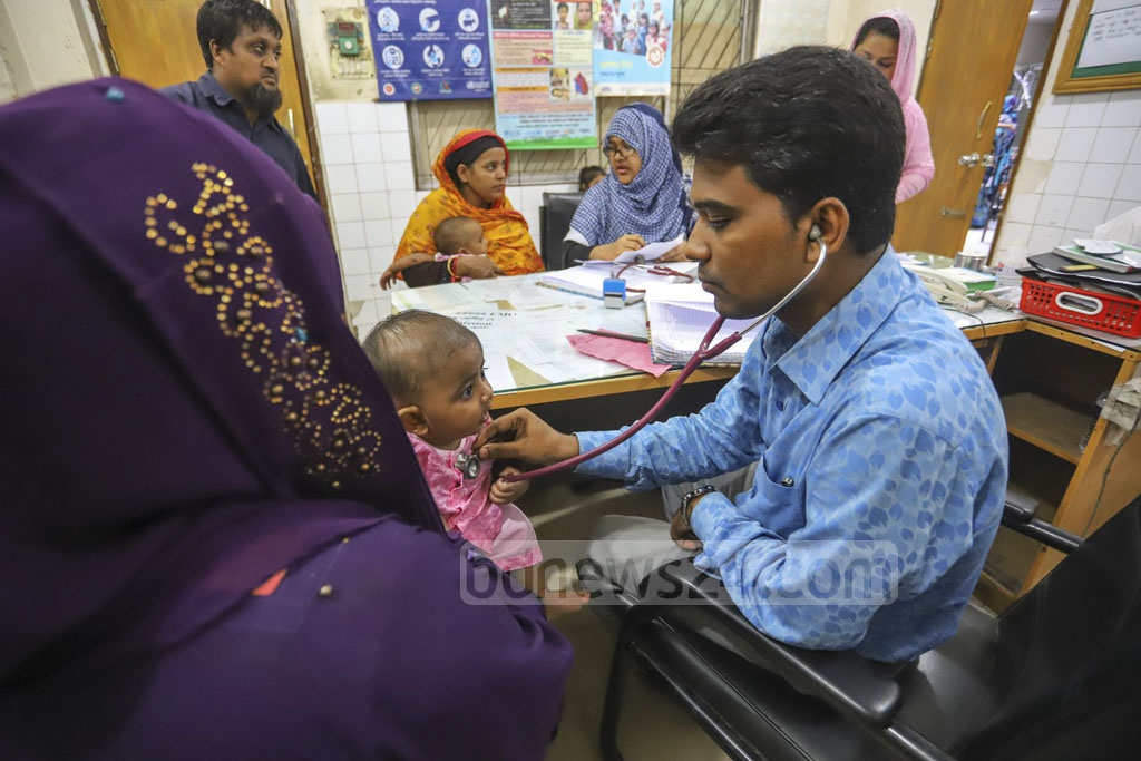 A doctor attending to a child down with fever at the Shishu Hospital's emergency department on Friday amid a dengue outbreak in Dhaka. Photo: Asif Mahmud Ove