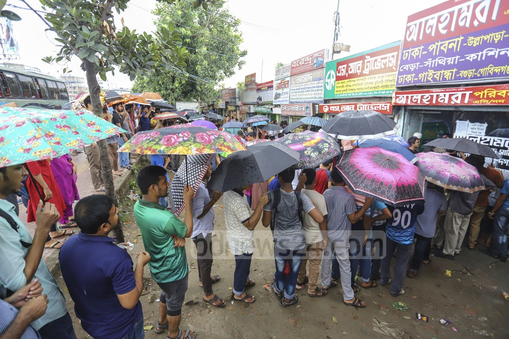 Braving the rain, people seeking advance bus tickets ahead of Eid-ul-Azha crowd Gabtoli Bus Terminal on Friday. Photo: Asif Mahmud Ove