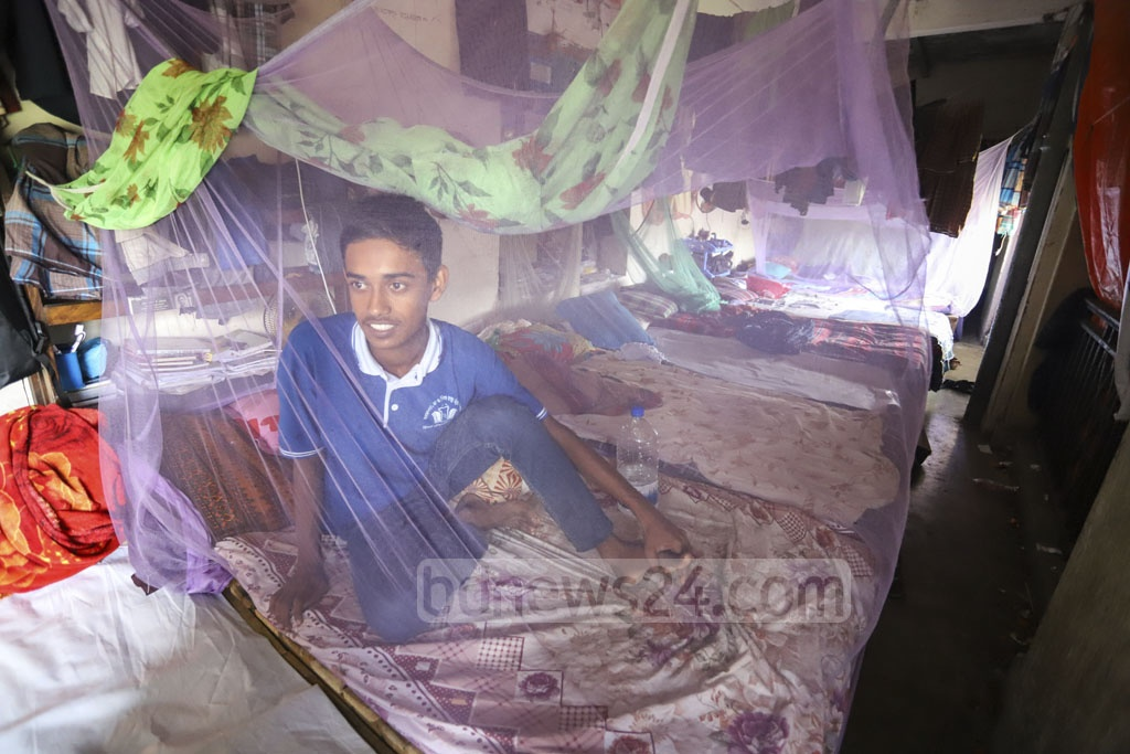 The SM Hall authorities of the Dhaka University have arranged seats for the first-year students on the veranda. They are staying inside mosquito nets even during daytime out of fear of dengue. This photo of Japanese studies student ASM Bukhari was snapped on Sunday. Photo: Asif Mahmud Ove