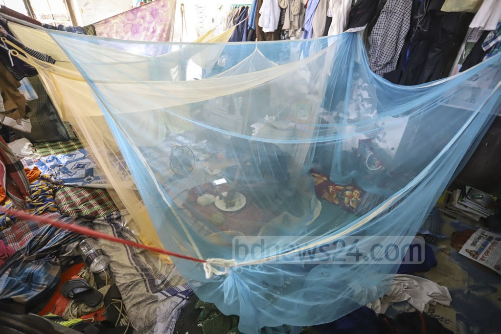 Mainul Islam, a first-year student of the Dhaka University's Bangla department, having his lunch inside a mosquito net at the SM Hall's veranda as death of one of the students after contracting dengue has sparked panic on the campus. Photo: Asif Mahmud Ove
