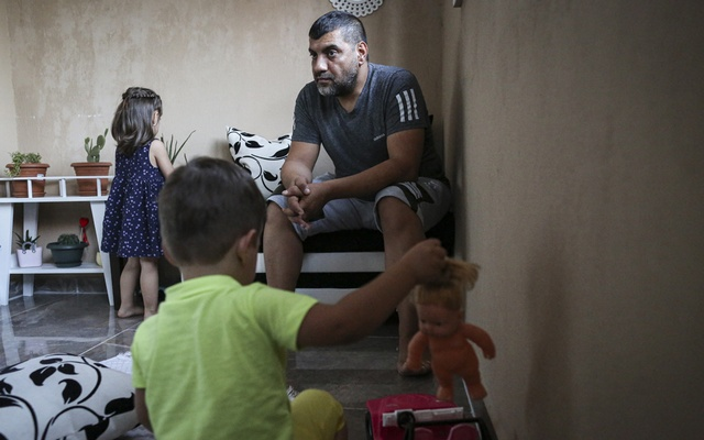 "Halit, 2, foreground, plays while his grandfather, Huseyin, watches at their home in Denizli, Turkey, July 1, 2019. Halit, whose mother has been sentenced to life in prison, is one of more than 200 Turkish children affiliated with the Islamic State who have been repatriated from Iraq. ""He had malaria and scabies,"" said Huseyin, who traveled to Baghdad four times to rescue his grandson. (Tara Todras-Whitehill/The New York Times)"
