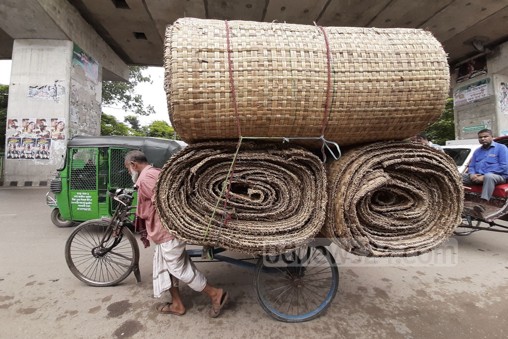 A man is snapped pulling a rickshaw-van loaded with mats used for sacrificing animals during Eid-ul-Azha from Old Dhaka's Showari Ghat to Karwan Bazar on Thursday. Photo: Abdullah Al Momin