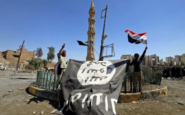 Shi'ite Popular Mobilisation Forces (PMF) members hold an Islamic State flag captured during a battle against Islamic State militants in Tal Afar, Iraq Aug 27, 2017. REUTERS