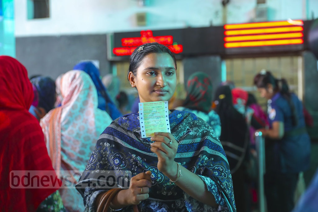 An overjoyed woman showing her ticket as she gets it to travel back home during Eid-ul-Azha after a long wait at the Kamalapur Raiway Station on Friday.