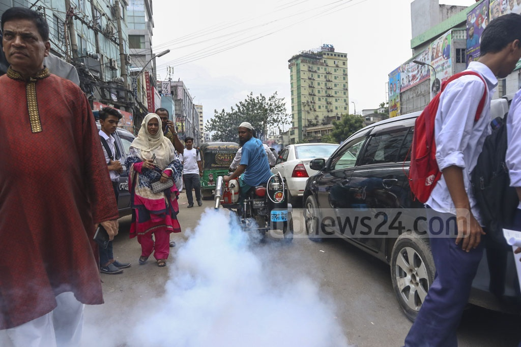 Dhaka City Corporation workers spray mosquito repellents in front of Ananda Cinema Hall at Farmgate in Dhaka on Saturday after the launch of a dengue awareness campaign. Photo: Mahmud Zaman Ovi