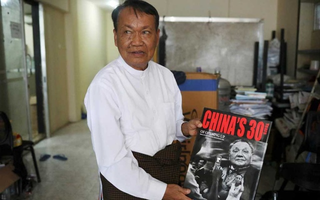 FILE PHOTO: Monywa Aung Shin, Editor-in-Chief of D Wave Journal, the magazine distributed by National League for Democracy Party (NLD), shows one of the books he got during his trip to China in his office in Yangon, Myanmar, Aug 1, 2019. REUTERS