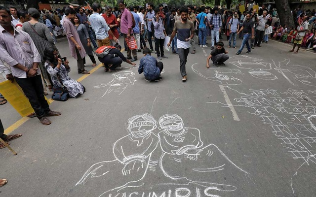 People draw and write messages on a road during a protest against the scrapping of the special constitutional status for Kashmir by the government, in New Delhi, India, Aug 7, 2019. REUTERS