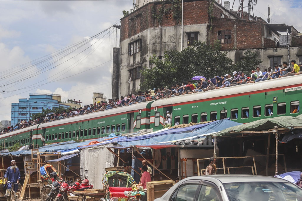 Holidaymakers leaving Dhaka on train roof before Eid-ul-Azha. This photo was clicked at Karwan Bazar on Friday.
