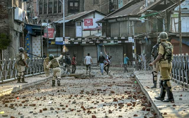Protestors throw rocks in the streets of Srinagar, where a strict curfew has been implemented following protests against Indian Prime Minister Narendra Modi's decision to revoke Kashmir's autonomy, in India, Aug. 8, 2019. (Atul Loke/The New York Times)