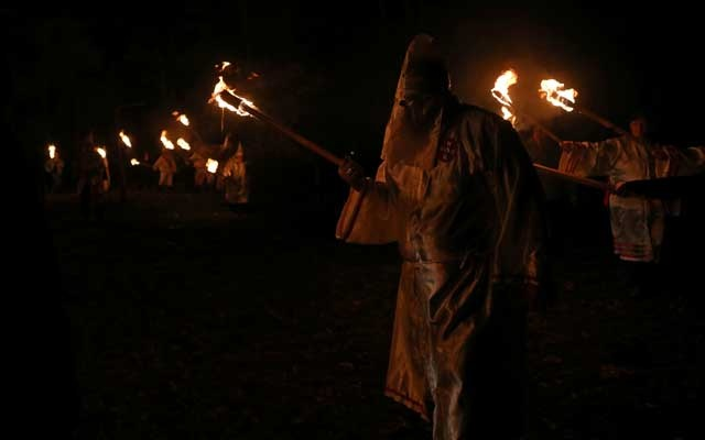 Members of the Loyal White Knights of the Ku Klux Klan carry torches at a cross-burning outside Yanceyville, North Carolina, US, November 4, 2017. The Loyal White Knights is one of the largest Klan groups in the United States, according to the Anti-Defamation League, which tracks extremist groups. REUTERS