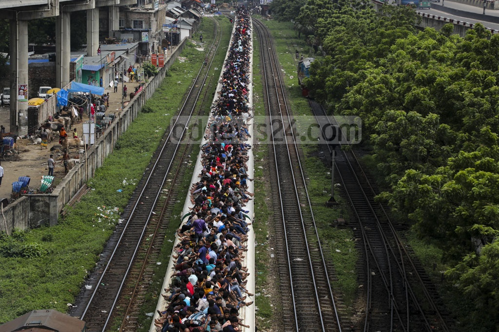 Residents of Dhaka are leaving the capital to celebrate Eid-ul-Azha with their loved ones. Many are risking their lives by riding on the roofs of trains due to overcrowded carriages. Photo: Mostafigur Rahman