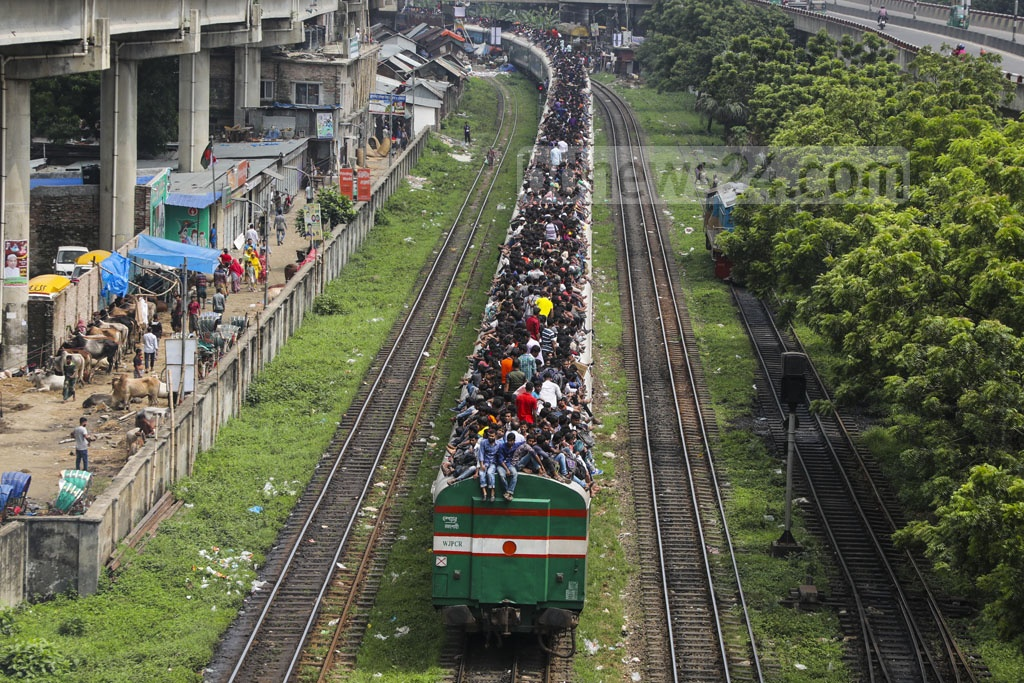 Eid holidaymakers putting their lives at risk by riding on top of overcrowded train carriages. The photo was taken from the Khilgaon flyover on Saturday. Photo: Mostafigur Rahman