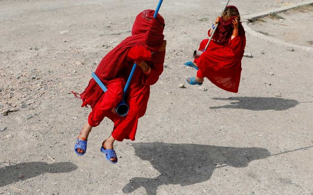 Afghan girls cover their faces as they ride on swings during the first day of the Muslim holiday of the Eid al-Adha, in Kabul, Afghanistan August 11, 2019.REUTERS/Mohammad Ismail
