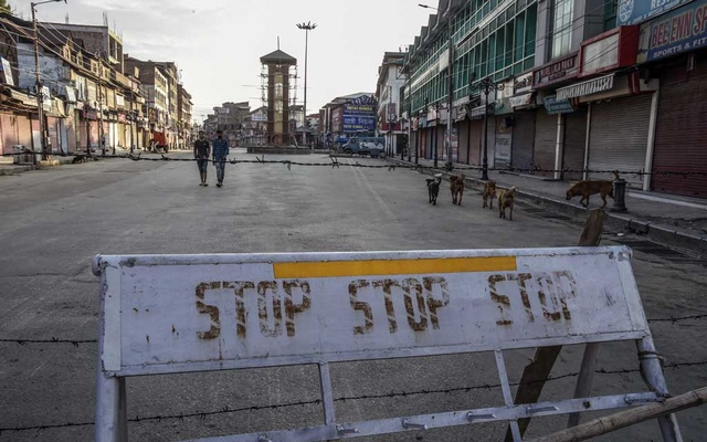 Pedestrians and stray dogs on a cordoned-off street in Srinagar, India, in the disputed region of Kashmir, on Thursday, Aug. 8, 2019. India's prime minister, Narendra Modi, addressed the nation Thursday night for the first time about his government's unilateral decision to revoke Kashmir's autonomy, speaking against a backdrop of rising protests, mass arrests and escalating tensions with Pakistan. (Atul Loke/The New York Times)