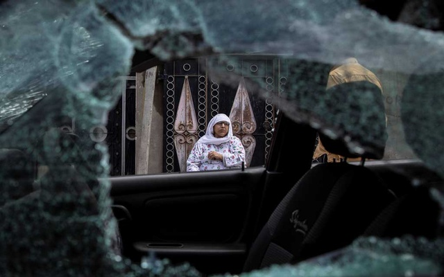 A woman, whose family car was allegedly damaged by Indian security forces after clashes between protesters and the security forces during restrictions, sits outside her house in Srinagar Aug 10, 2019. The clashes occurred on Friday, after the scrapping of the special constitutional status for Kashmir by the government. REUTERS/Danish Siddiqui