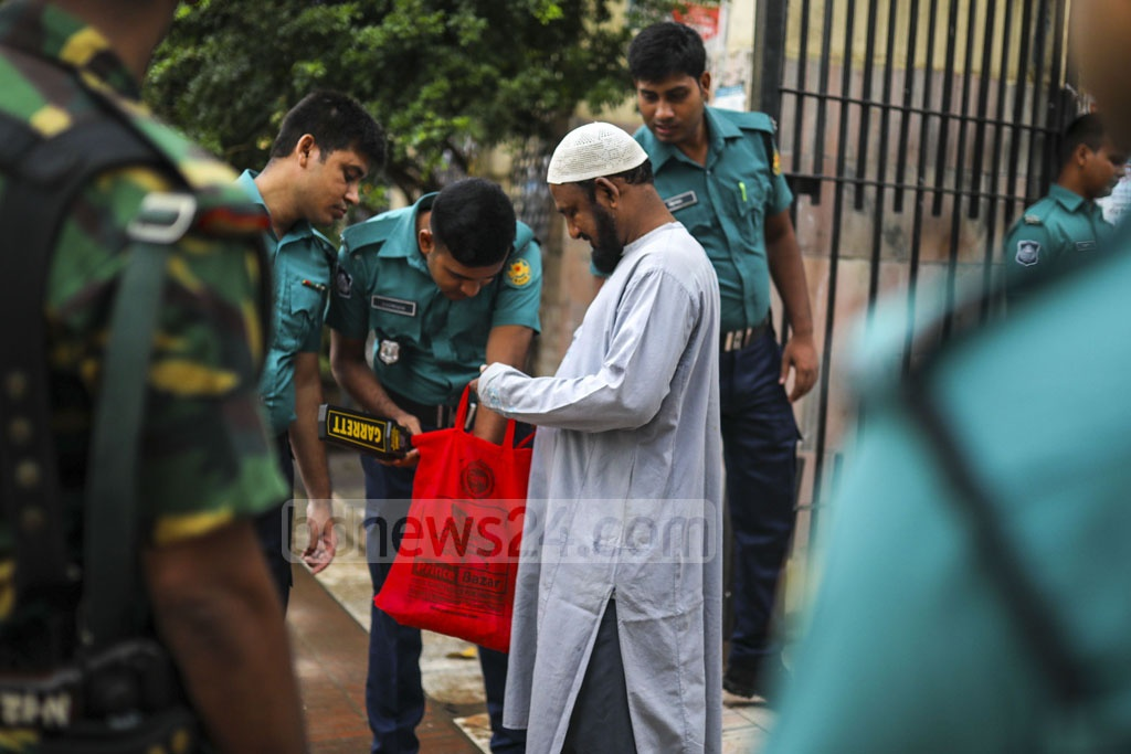 Law enforcers searching the bag of a worshipper outside Baitul Mukarram as part of the strict security measures surrounding first Eid congregation on Monday. Photo: Mostafigur Rahman