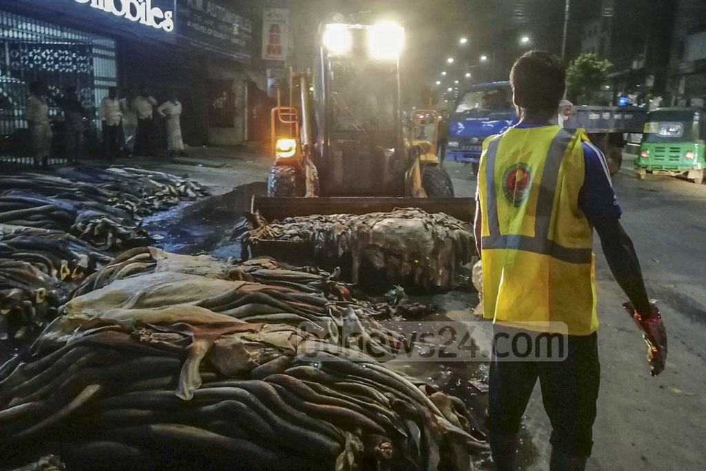 Chattogram City Corporation workers removing rawhides of cattle slaughtered on Eid-ul-Azha from a street in Chowmohani area on Tuesday. Seasonal traders dumped the rawhide on the street alleging they were not getting fair price. Photo: Sumon Babu
