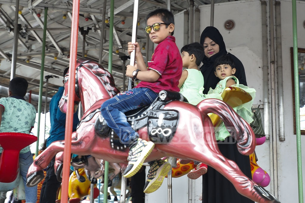 Children enjoying a ride during their visit to Shishu Mela at Dhaka's Mirpur Road in Shyamoli on Tuesday, a day after the Eid-ul-Azha. Photo: Abdullah Al Momin