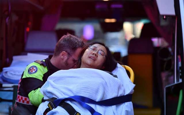 A woman is taken by ambulance, as police officers investigate a scene following reports of a stabbing in Sydney, Australia, Aug 13, 2019. Dean Lewis/AAP/via REUTERS