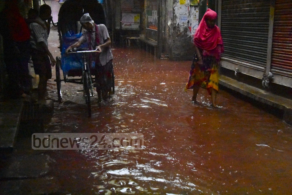 Blood-stained water streaming down a street in old Dhaka's Bangshal area amid rains on Wednesday, two days after Eid-ul-Azha.