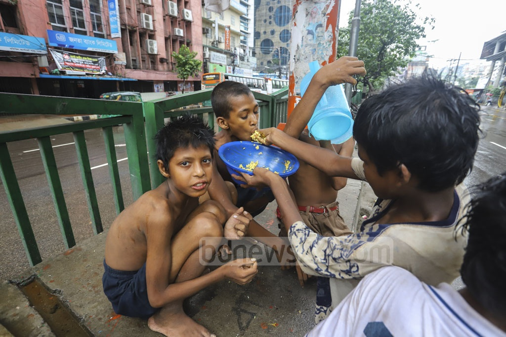 Street children demonstrate their unyielding unity by sharing a meal on a footbridge at Motijheel in Dhaka. Photo: Asif Mahmud Ove