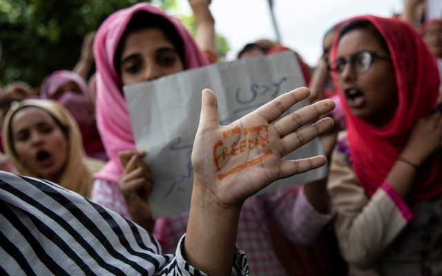A Kashmiri woman shows her hand with a message as others shout slogans during a protest after the scrapping of the special constitutional status for Kashmir by the Indian government, in Srinagar, Aug 11, 2019. REUTERS
